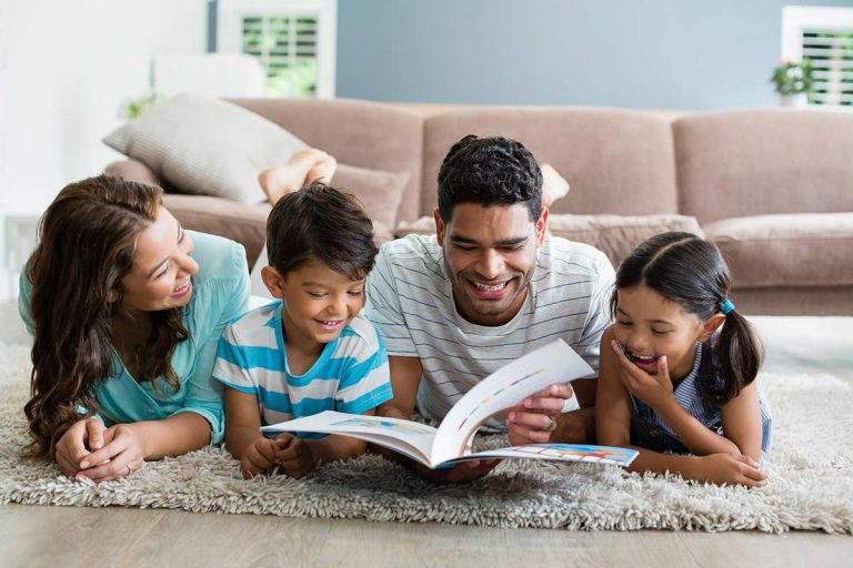Parents and children lying on rug reading book